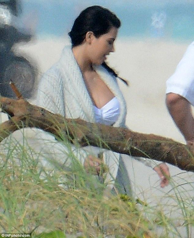 Kim Kardashian covers her bump with a loose cardigan as she makes her way to bikini