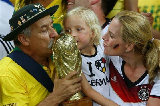 بالصور مشجع برازيلي يهدي كأس العالم لمشجعة ألمانية صغيرة 2014